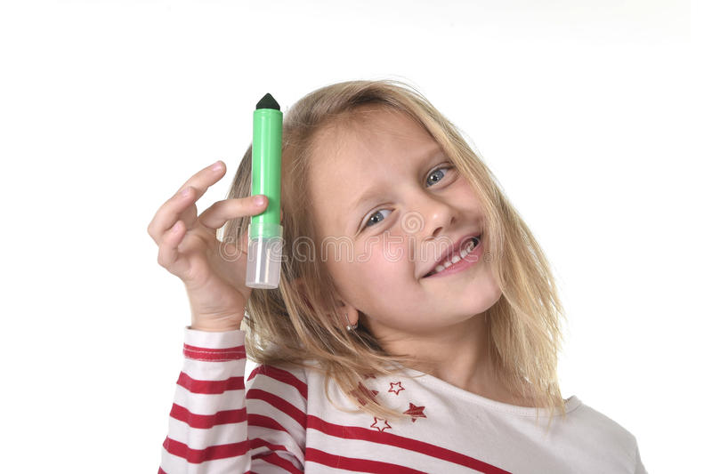 Sweet beautiful female child holding drawing and writing marker school supplies concept stock image