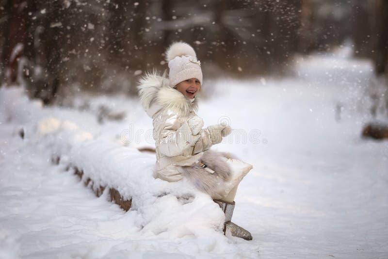 Sweet beautiful girl enjoying falling snowflakes in the park for walk royalty free stock image