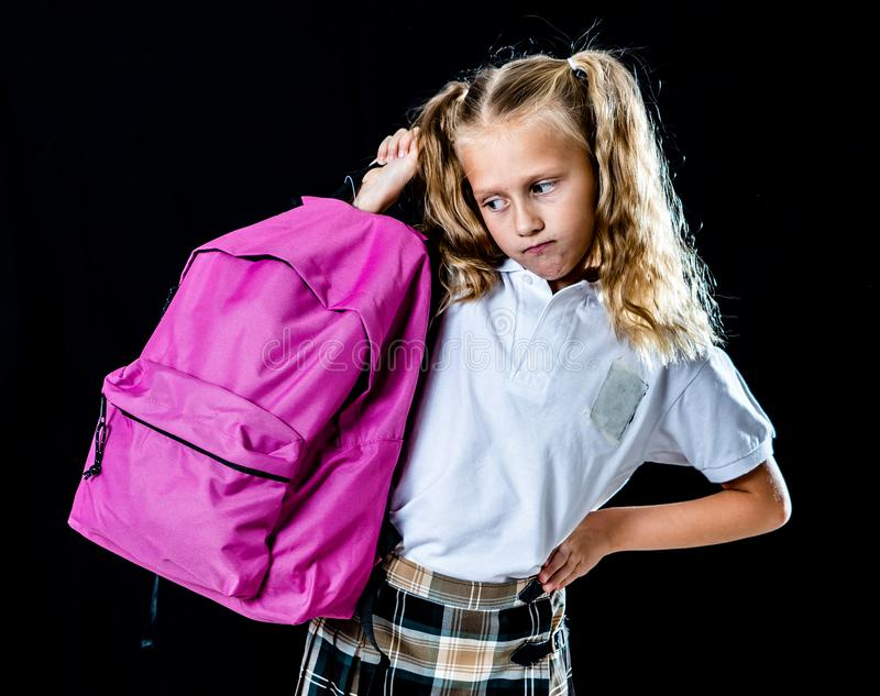 Sweet beautiful little girl in school uniform feeling angry and frustrated looking at the camera isolated on black background in stock images