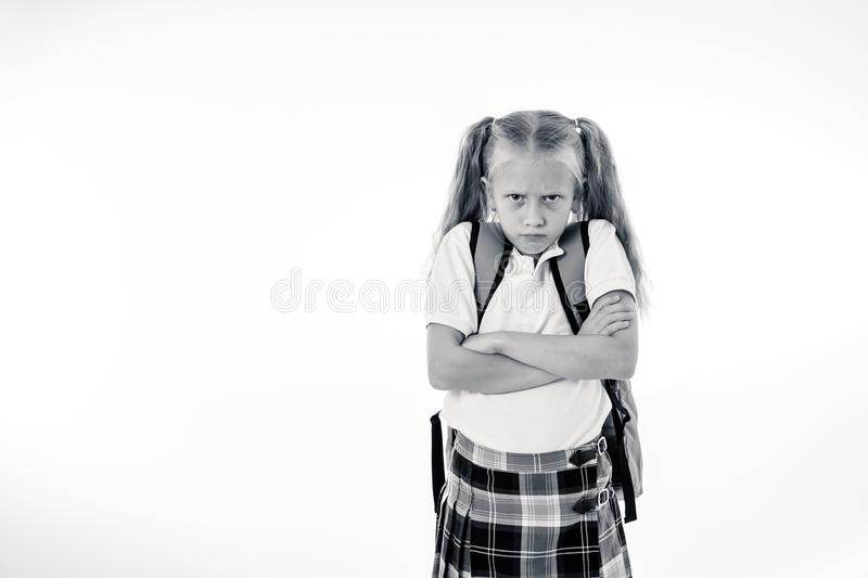 Sweet beautiful little girl in school uniform feeling angry and frustrated looking at the camera isolated on white background in stock images