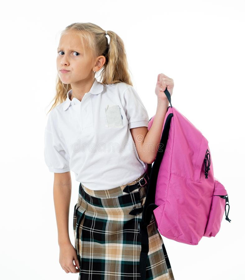 Sweet beautiful little girl in school uniform feeling angry and frustrated looking at the camera isolated on white background in royalty free stock photo