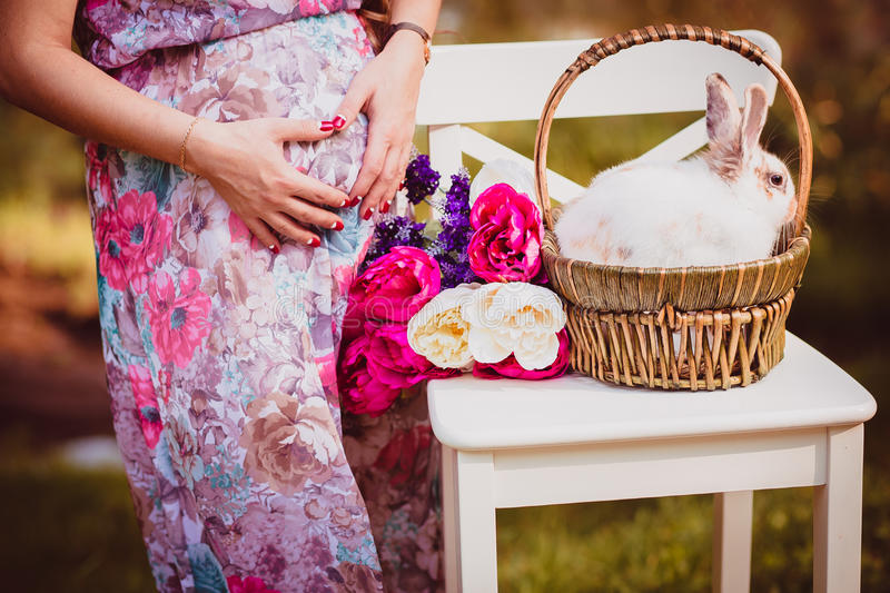 Sweet beautiful pregnant woman with flowers and Easter bunny stock images