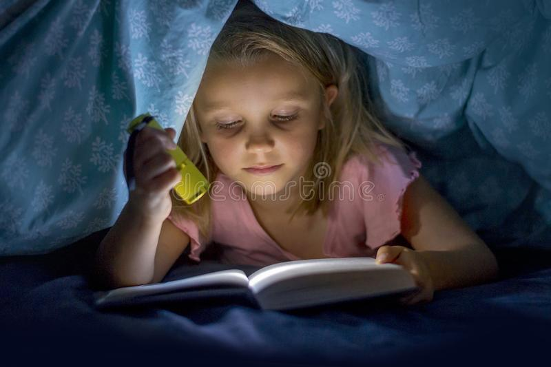 Sweet beautiful and pretty little blond girl 6 to 8 years old under bed covers reading book in the dark at night with torch light royalty free stock image