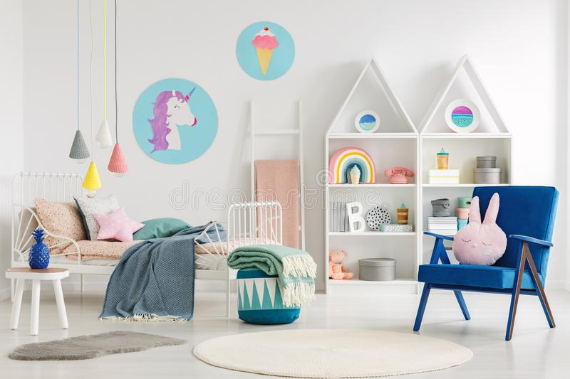 Sweet bedroom interior for a kid with a blue armchair, rabbit pi. Llow, bed, unicorn, ice-cream posters and shelves stock photo