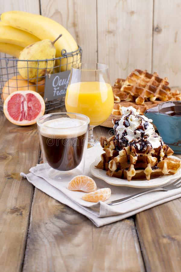 Sweet Belgian waffles for breakfast, decorated with white cream and chocolate sauce. Glass with coffee black and orange juice, royalty free stock images