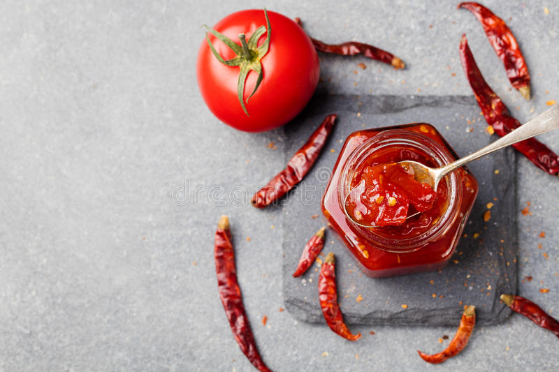 Sweet bell pepper and chili pepper sauce, confiture, jam in a glass jar. Top view. Copy space. Sweet bell pepper and chili pepper sauce, confiture, jam in a royalty free stock image