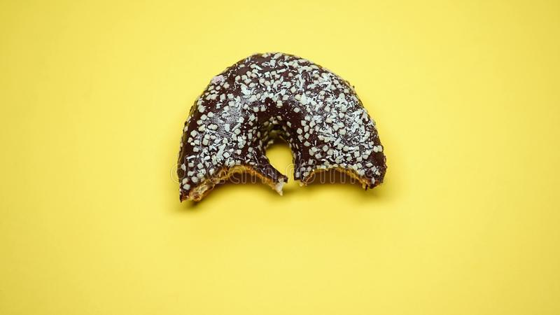 Sweet bitten donut, overeating and bulimia problems, junk food addiction, macro. Stock photo royalty free stock image