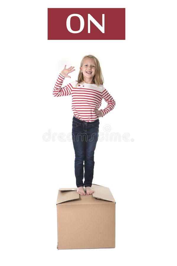 Sweet blond hair child stading on top of cardboard box isolated on white background in learning english. Cute and sweet blond hair child stading on top of stock images