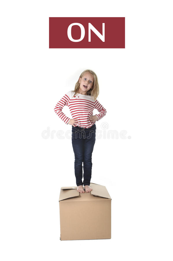 Sweet blond hair child stading on top of cardboard box isolated on white background in learning english. Cute and sweet blond hair child stading on top of stock photography