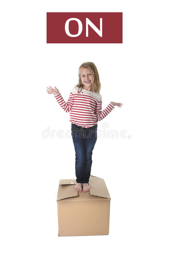 Sweet blond hair child stading on top of cardboard box isolated on white background in learning english. Cute and sweet blond hair child stading on top of stock photos