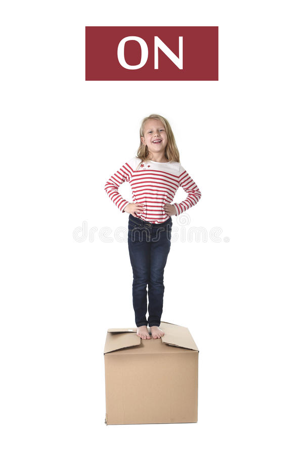 Sweet blond hair child stading on top of cardboard box isolated on white background in learning english. Cute and sweet blond hair child stading on top of royalty free stock photo