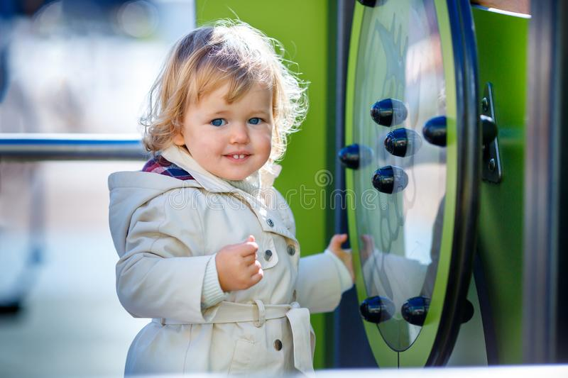 Sweet blond little baby girl in hooded trench coat plays outdoors at playground royalty free stock images