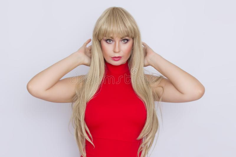 Sweet blonde woman with long hair in red evening dress over grey background. Wearring on celebration. Sweet beautiful blonde woman with long hair in red evening stock images