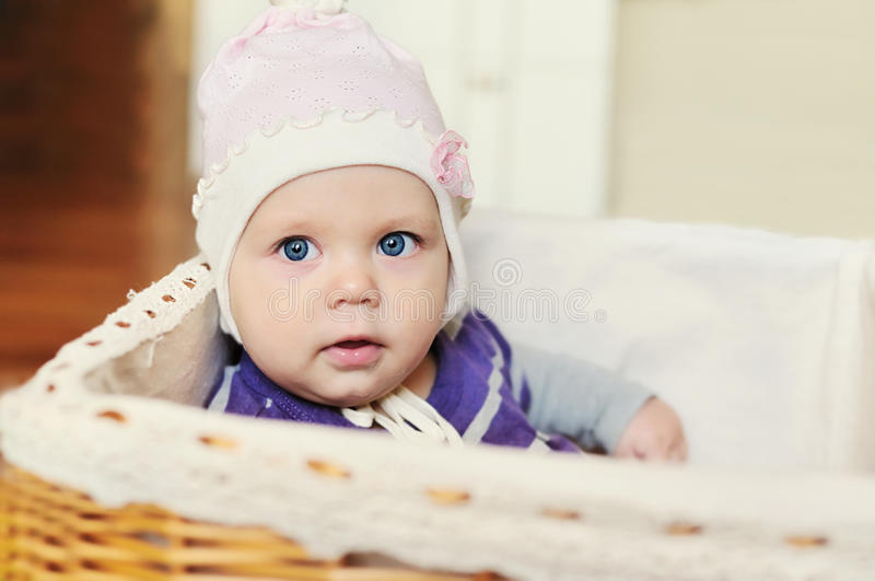 Sweet blue-eyed baby in basket stock images
