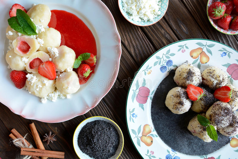 Sweet boiled dumplings filled with strawberries with a poppy seed sauce and curd. Two plates of sweet boiled dumplings filled with strawberries with a poppy seed stock photo