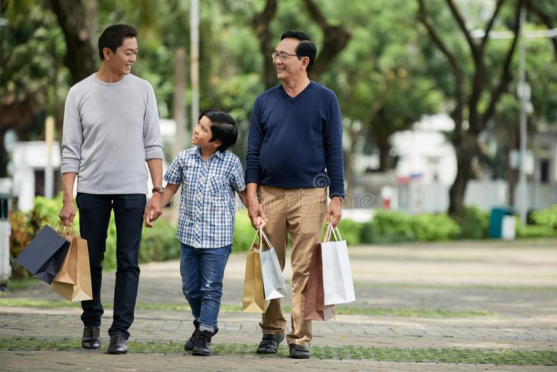 Boy walking with father and grandfather after shopping royalty free stock photos
