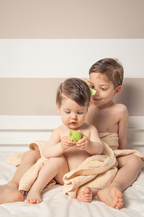 Sweet boy combing little girl in a bed after bath. Portrait of sweet boy combing little girl under the towel playing with toy over a bed after bath stock photography