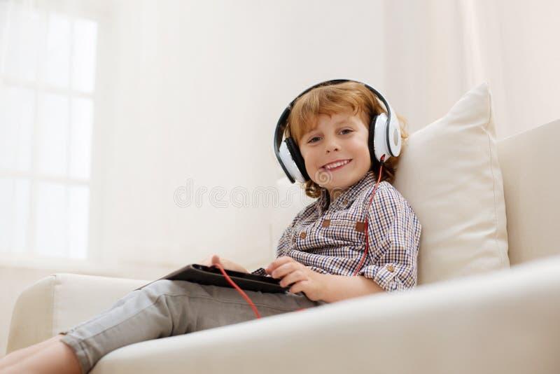 Sweet bright boy enjoying some music royalty free stock photos