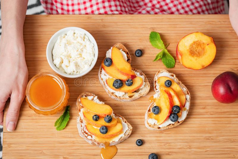 Sweet bruschetta with ricotta, peach and honey royalty free stock images