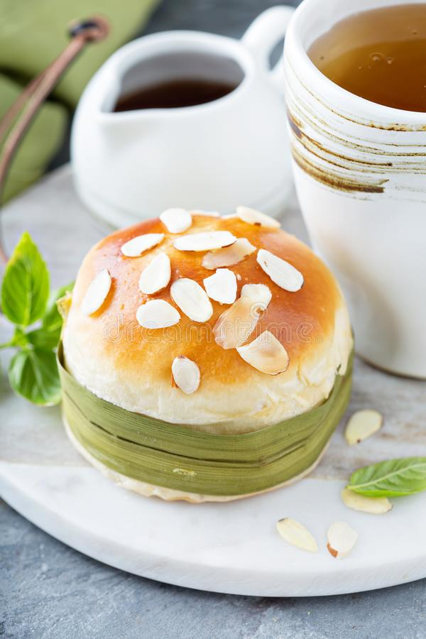 Sweet bun with almonds. Served with green tea stock photography