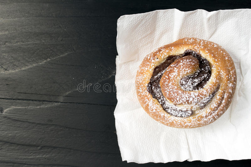 Sweet bun. On black wooden background royalty free stock image