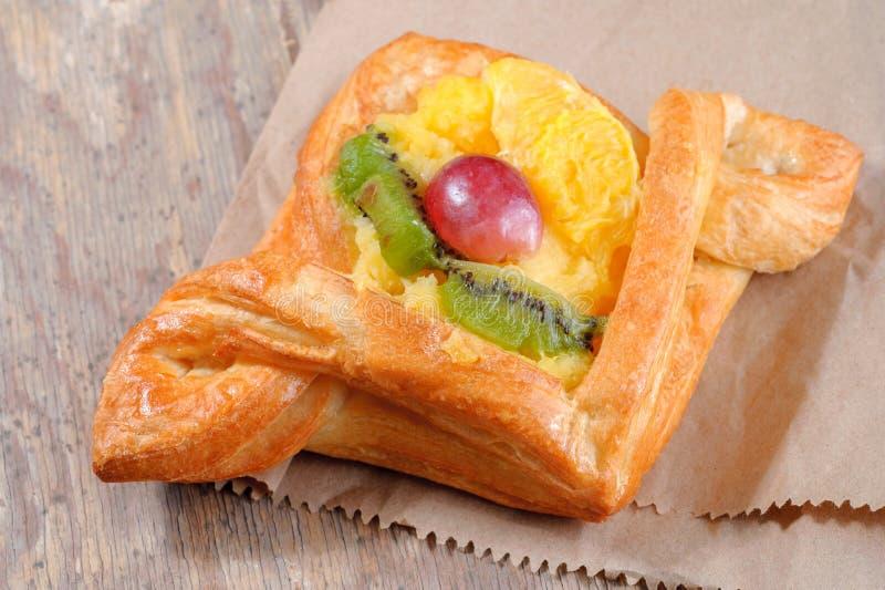 Sweet bun with orange kiwi and grapes stock images