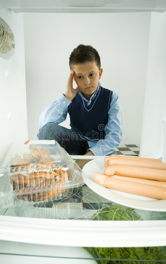 Sweet bun or weiners. Young boy sitting oposite fridge and thinking about somethig. Front view royalty free stock photos