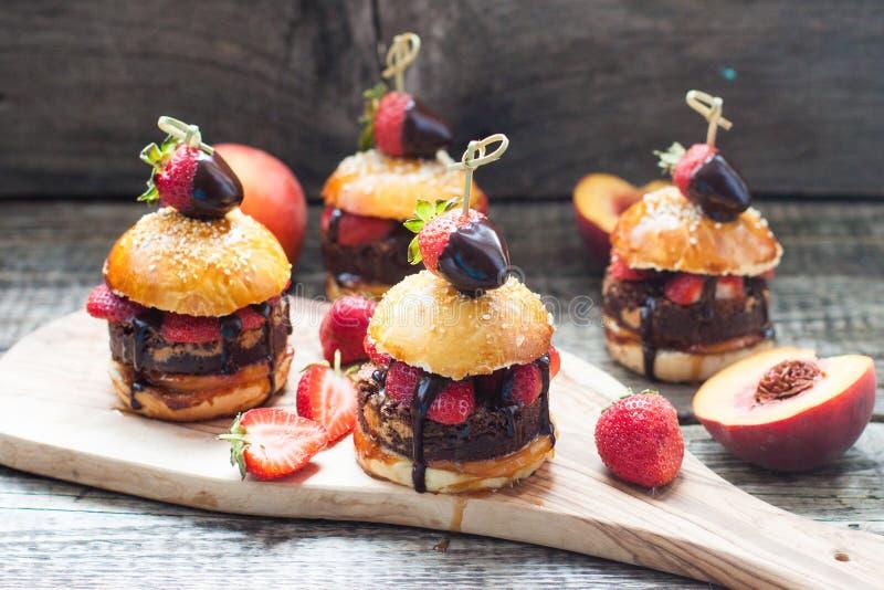 Sweet burgers with brioche bun, chocolate brownie layer, fresh strawberries and chocolate sauce. Sweet burgers with brioche bun, chocolate brownie layer, fresh stock photography