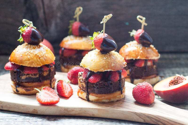 Sweet burgers with brioche bun, chocolate brownie layer, fresh strawberries and chocolate sauce. Sweet burgers with brioche bun, chocolate brownie layer, fresh royalty free stock images