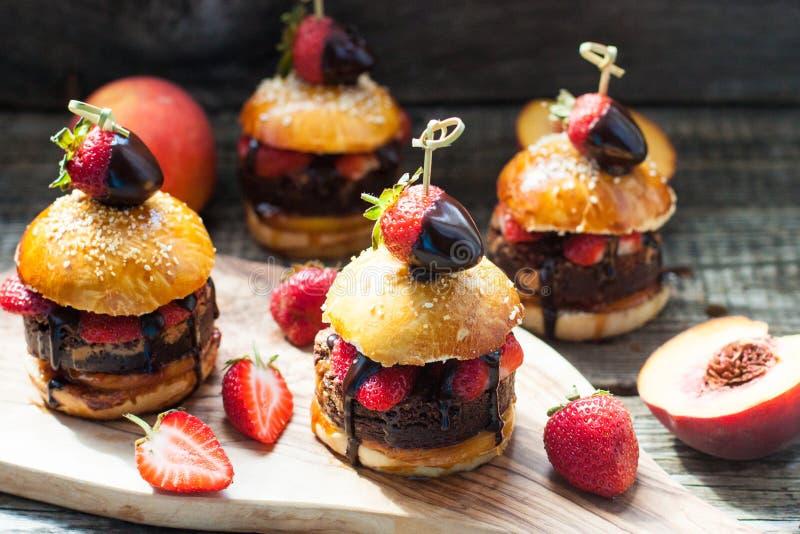 Sweet burgers with brioche bun, chocolate brownie layer, fresh strawberries and chocolate sauce. Sweet burgers with brioche bun, chocolate brownie layer, fresh royalty free stock photos