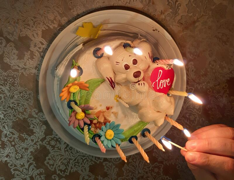 Sweet cake with candles. A hand holds a match with fire for lighting candles on cake. Sweet cake with candles. A hand holds a match with fire for lighting royalty free stock photos