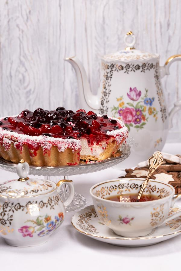 Sweet cake with cherry jelly, tasty and fresh. Antique tea set. Antique floral tea set on a white tablecloth and sweet cake with cherry jelly, tasty and fresh royalty free stock photo
