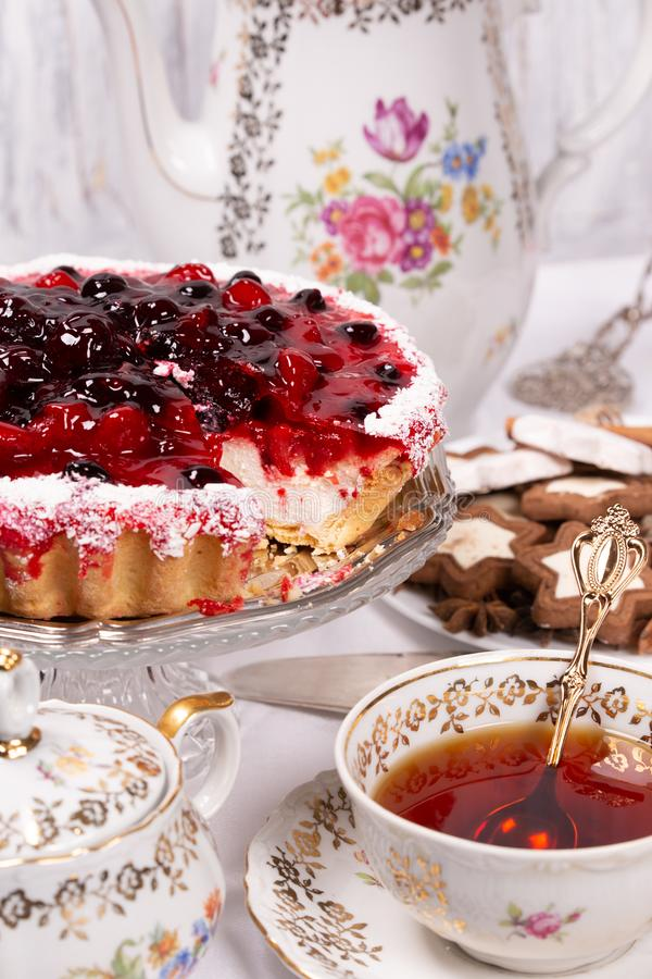 Sweet cake with cherry jelly, tasty and fresh. Antique tea set. Antique floral tea set on a white tablecloth and sweet cake with cherry jelly, tasty and fresh stock photography
