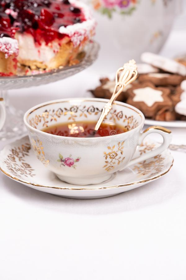 Sweet cake with cherry jelly, tasty and fresh. Antique tea set. Antique floral tea set on a white tablecloth and sweet cake with cherry jelly, tasty and fresh stock images