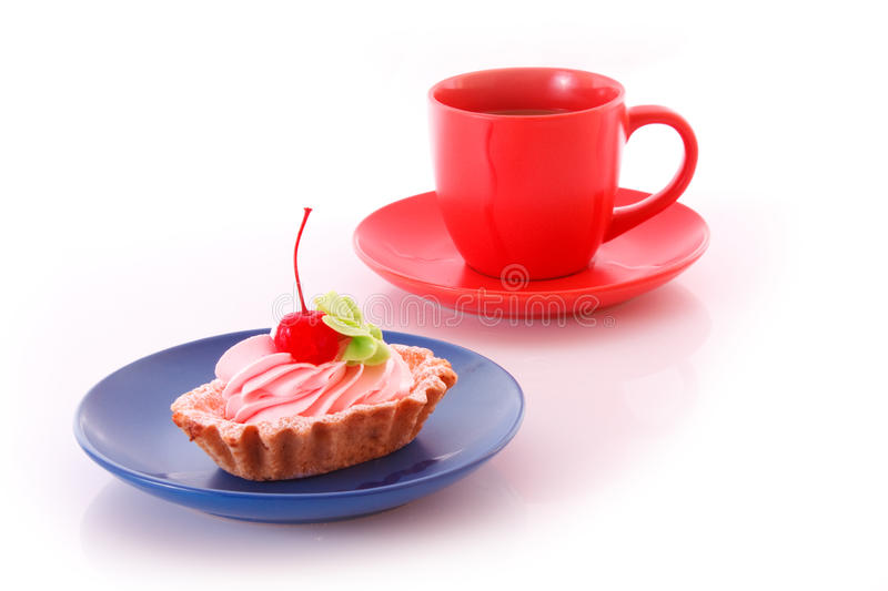 Sweet cake with cherry with red cup isolated. On white royalty free stock images