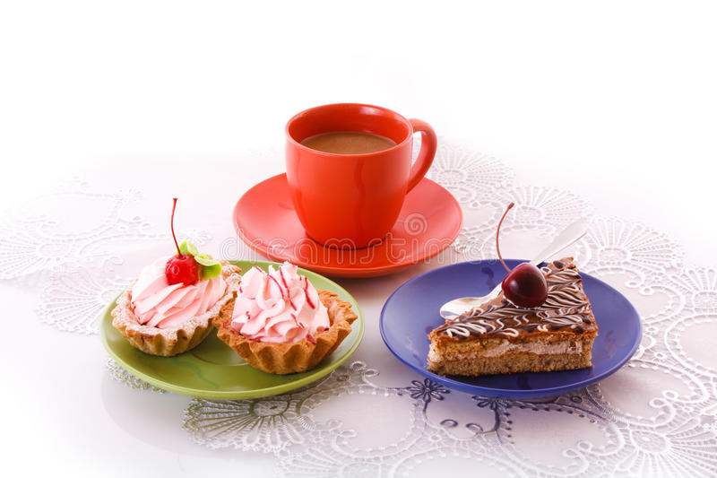 Sweet cake with cherry with red cup isolated. On white stock image