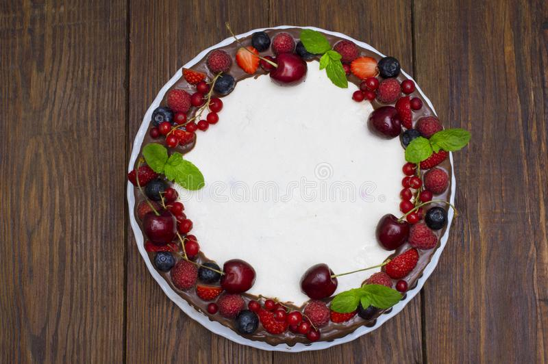 Sweet Cake with fresh berries on wooden background. Top view stock photography