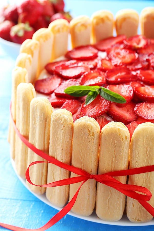 Sweet cake with strawberries. On plate on blue wooden background royalty free stock photo