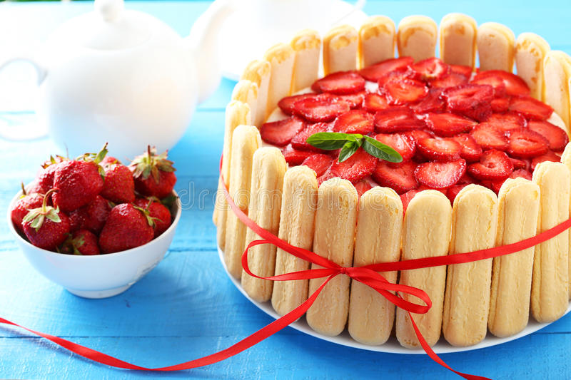 Sweet cake with strawberries. On plate on blue wooden background stock photography