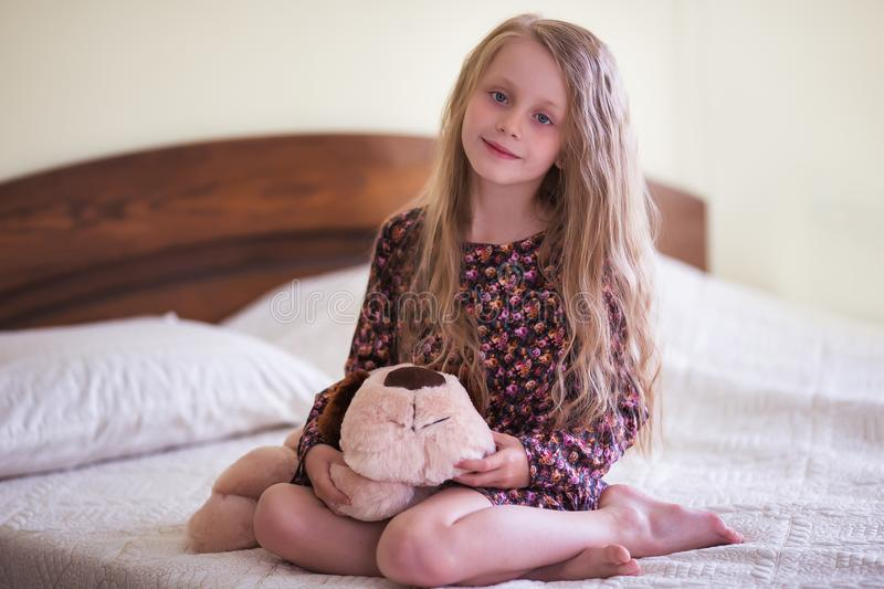 Sweet calm girl with a soft toy Sidley on the bed in the bedroom royalty free stock images