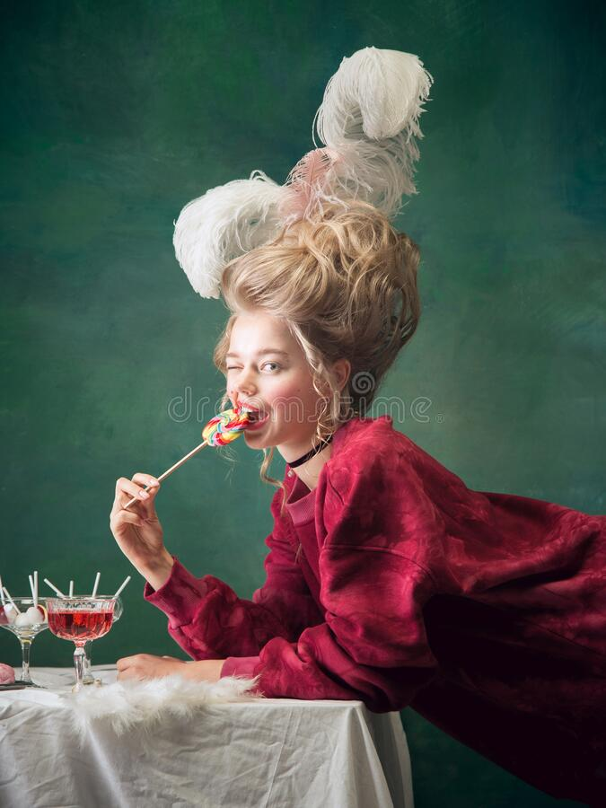Young woman as Marie Antoinette on dark background. Retro style, comparison of eras concept. Sweet candy, playful mood. Young woman as Marie Antoinette on dark stock photography
