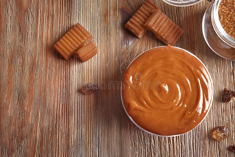 Sweet caramel candies and bowl with sauce royalty free stock photo