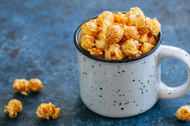 Sweet caramel pop corn in a jar on a blue stone background. Close up. royalty free stock photo