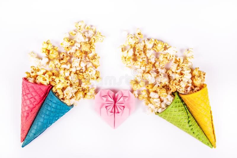 Sweet caramel popcorn and paper heart. Copy space. Origami heart of pink paper. Bright festive sweets. stock photos