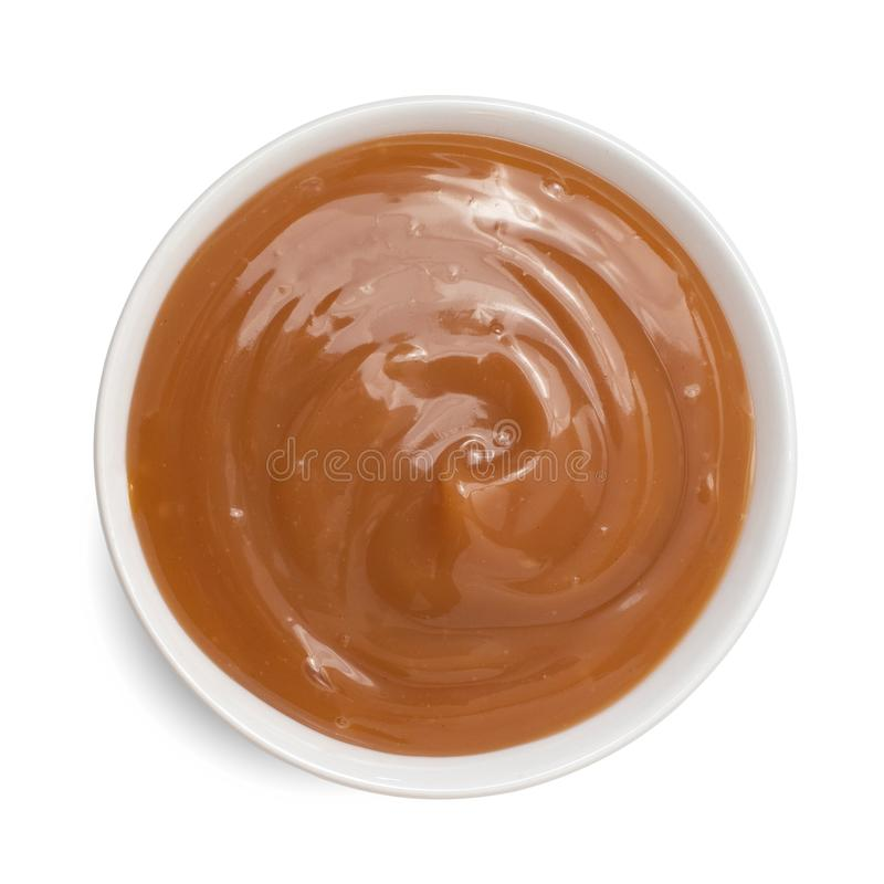 Sweet caramel sauce in bowl isolated on white background. Top view stock photos