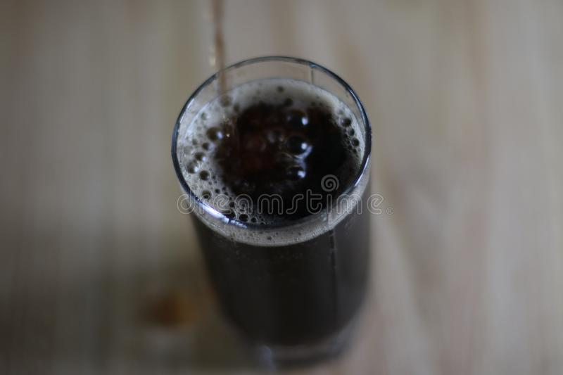 Sweet carbonated drink is pouring into glass cup royalty free stock images