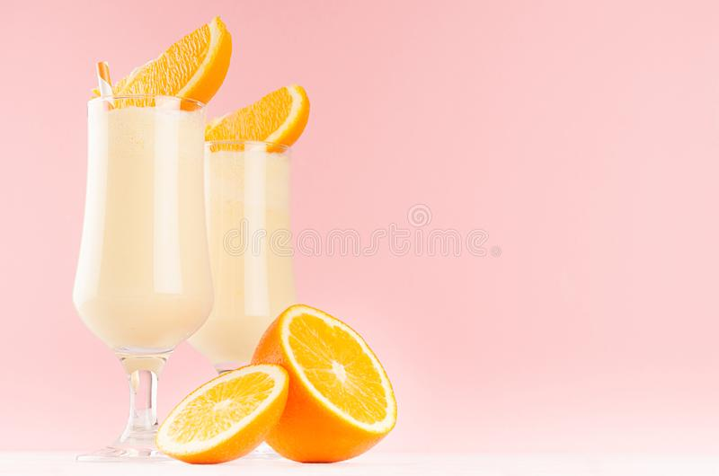 Sweet cheerful milkshakes decorated slices fruit, striped straws on light pastel pink background. Sweet cheerful milkshakes decorated slices fruit, striped stock images