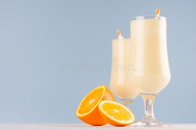 Sweet cheerful oranges milkshakes in two glass decorated slices fruit, striped straws on light pastel blue background. Sweet cheerful oranges milkshakes in two stock image