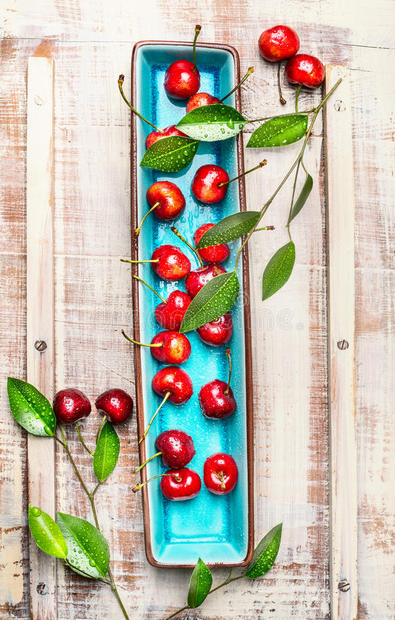 Sweet cherries with green leaves on blue rectangular plate on light wooden rustic background, top view. Summer fruits and berries concept royalty free stock photography