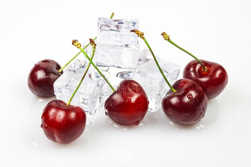 Sweet cherries with ice cubes, yes against a white background royalty free stock image